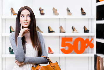 Portrait of woman in shopping center with 50% sale