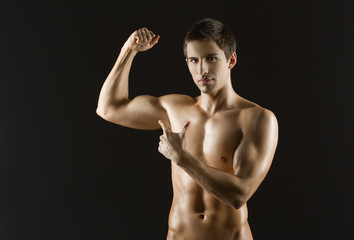 Naked sportsman pointing at his bicep, isolated on black