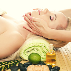 A beautiful young woman receiving facial massage at a spa salon