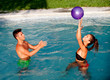 Happy couple relaxing in the pool playing with a ball