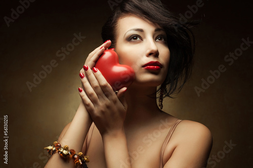 Portrait of fashionable model with red lips holding heart