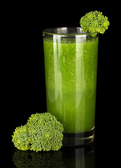 Green vegetable juice in glass isolated on black