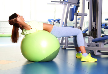 Pretty sporty girl do physical exercises on fit-ball in gum