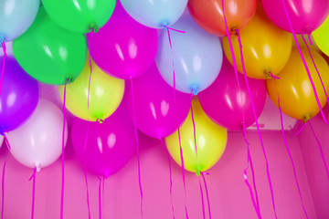 Colorful balloons on pink wall background