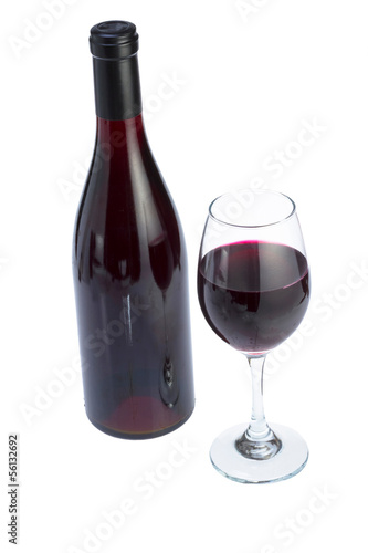Glass full of red wine and bottle.