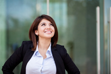 Happy businesswoman looking up