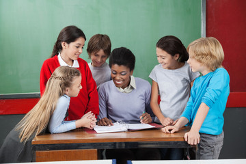 Female Teacher Teaching Schoolchildren At Desk