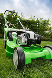 Green lawnmower on green lawn.