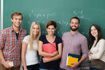 lächelnde studenten stehen vor der tafel