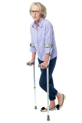 Aged woman in pain walking with crutches