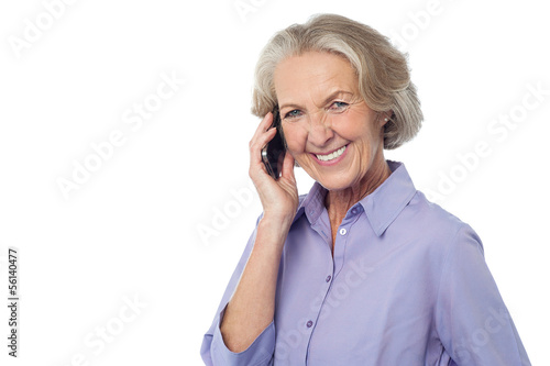 Senior smiling lady attending phone call