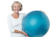 Senior woman posing with exercise ball