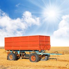 A empty tractor trailer on a wheat field.