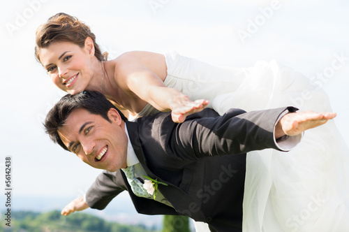 Bride and groom piggyback