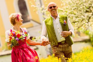 Hochzeitspaar in Tracht  läuft gemeinsam über Wiese