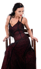 an elegant woman dressed in a dark red dress sits in a chair