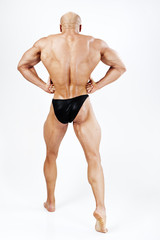 Man very well muscular in the bodybuilding pose of the strongman