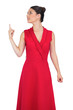 Cheerful glamorous model in red dress pointing up