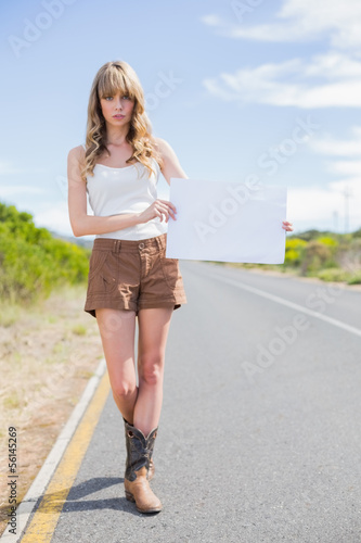 Serious woman holding sign while hitchhiking