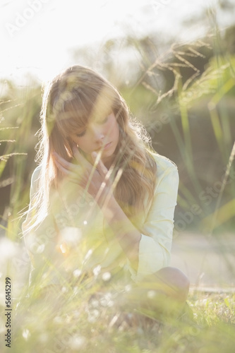 Blonde hipster girl sitting on the grass