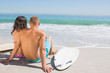 Cute young couple with their surfboards looking at the sea