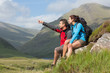 Couple taking a break after hiking uphill with man pointing
