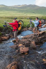 Couple crossing a stream holding their mountain bikes