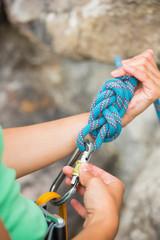 Female rock climber adjusting her harness