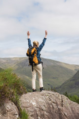 Woman standing on rock cheering after a hike