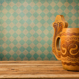 Wooden beer mug on wooden table over retro wallpaper