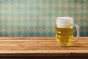 Beer on wooden table over retro wallpaper