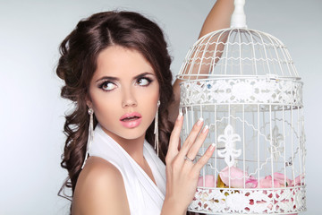 Concept photo of amazed woman holding vintage bird cage isolated