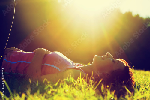 Young pretty woman lying on the grass at summer sunset - 56147425