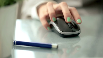 Woman hand using wireless mouse on reflective table
