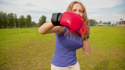 The girl in boxing gloves in a meadow