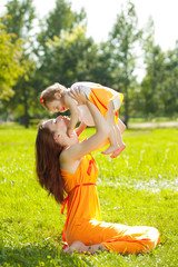 Beauty Mom and baby outdoors. Happy family playing in nature. Mo