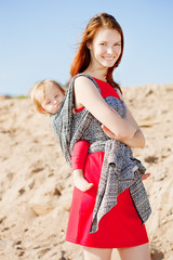 Beautiful woman with a baby in a sling. Mom and baby. Mother and