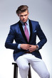 seated young business man taking his jacket off