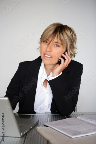 Blond businesswoman working away at her desk