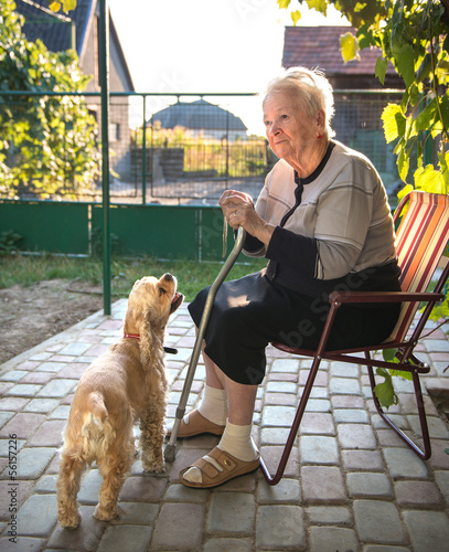 Old woman sitting on a chair with a cane