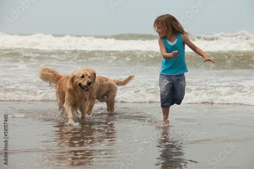 girl with dogs by the ocean