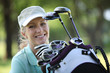 woman with a bag full of golf clubs