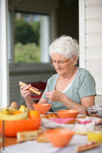 Senior woman eating on her terrace