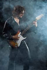 Psychedelic rock guitarist with long brown hair and beard. Dress