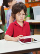 Little Boy Using Digital Tablet In Kindergarten