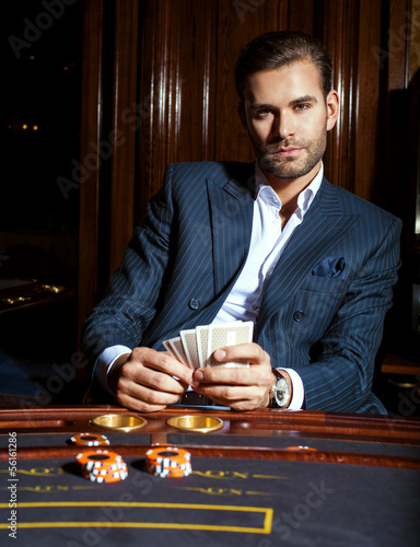 man in a suit player sits with cards in a hand