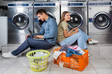 Couple Using Laptop And Earphones At Laundry