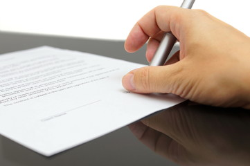 businessman examines the articles of agreement before signing