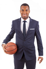 Smiling Young business man holding a basketball, isolated on whi