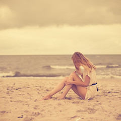 beautiful girl sitting on the shore of the ocean